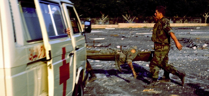 A Marine carries a wounded servicemember on October 23, 1983 in Beirut, Lebanon