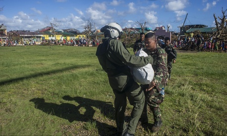 A Naval Aircrewman delivers relief supplies to a Filipino Army soldier