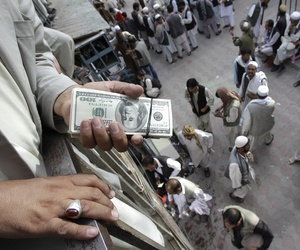 A trader holds a bundle of dollar bills in a market in Afghanistan