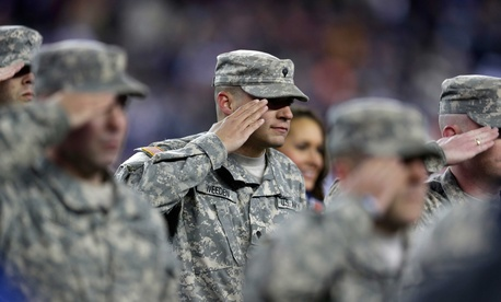 A soldier salutes active duty troops and veterans at a ceremony conducted during a football game between the Denver Broncos and the New England Patriots