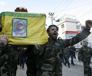 "Hezbollah fighters in Lebanon carry the coffin of their commander Ali Bazzi, killed in Syria executing his ""jihadi duties,"" in this photo from Dec. 9, 2013."