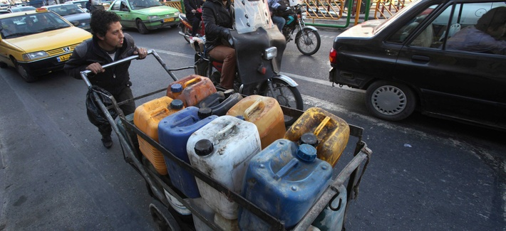 A boy pushes a cart loaded with fuel containers in Tehran, Iran