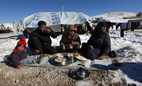Syrian refugees eat lunch in a camp in eastern Lebanon