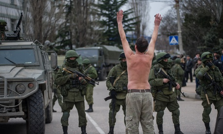 A protester stands bare in front of Russian-marked vehicles in Balaklava, near Sevastopol, Ukraine, on Saturday.