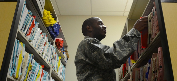An airman files patient health records at Langley Air Force Base, Va.