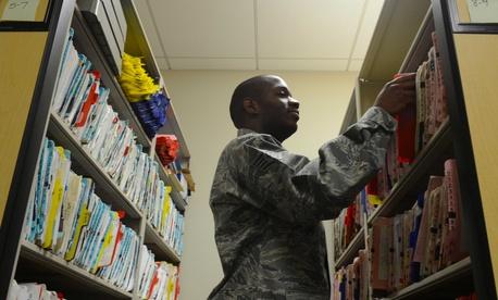 An airman files patient health records at Langley Air Force Base, Va.