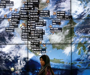 A traveller stands in front of a flight information board at Kuala Lumpur International Airport