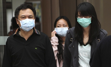 People cover up to protect from bird flu in Taipei, Taiwan, Friday, Apr. 26, 2013.