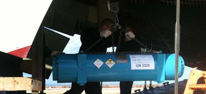 An NNSA employee loading a cask of HEU onto a cargo plane