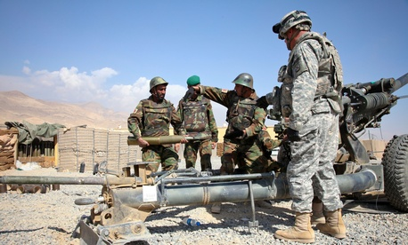 An ANA soldier carries a 105 mm round while training on an M119 Howitzer