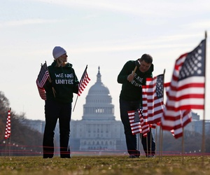 Two military veterans with the Iraq and Afghanistan Veterans of America (IAVA) placing 1892 flags on the National Mall to represent veterans and service members who have died by suicide in 2014