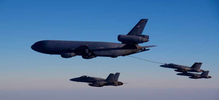 A KC-10A tanker refuels one of the Navy's F/A 18 fighter jets