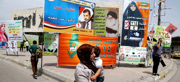 An Iraqi woman walks past a series of billboards advertising election candidates in Iraq