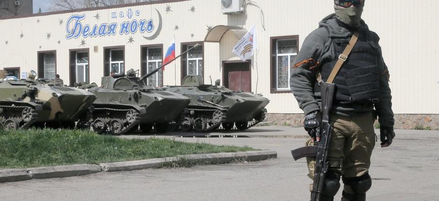 A masked pro-Russian gunman guards combat vehicles in Donetsk, Ukraine
