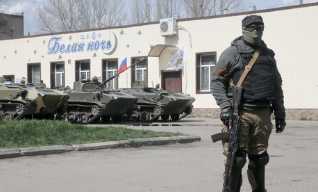 A masked pro-Russian gunman guards combat vehicles in Donetsk, Ukraine