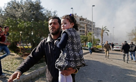 A Lebanese man carries an injured girl away from a car bombing in the suburbs of Beirut, Lebanon