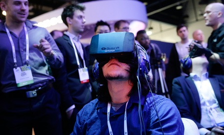 An attendee at the International Consumer Electronics Show trying on the Oculus headset