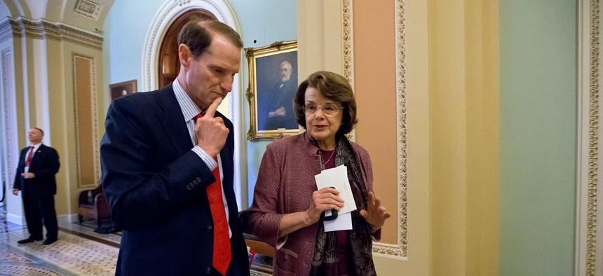 Sen. Ron Wyden, D-Ore., walks with Sen. Dianne Feinstein, D-Calif. on Capitol Hill in June 2013.