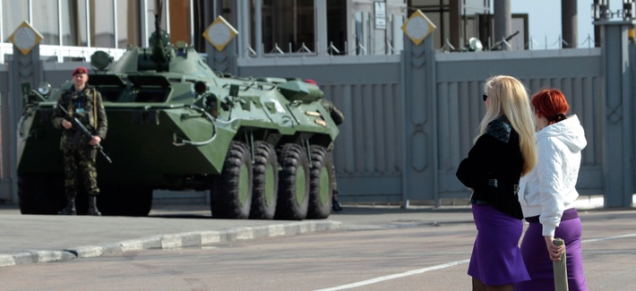 Two Ukrainian women walk past an armored personnel carrier in Kiev, Ukraine.