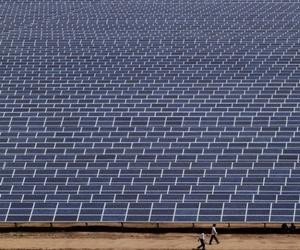 Indian workers walk past solar panels at the 200 megawatt Gujarat Solar Park.
