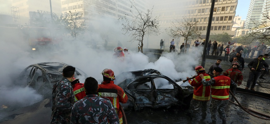 Lebanese firefighters arrive at the scene of a car bomb in Beirut, Lebanon, Dec. 27, 2013.