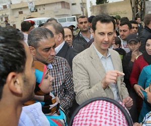 Syrian president Bashar al-Assad speaks to citizens during a visit to a village outside of Damascus, Syria, April 20, 2014.