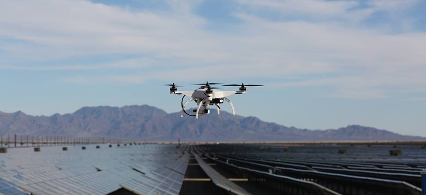 One of Skycatch's quadcopter drones hovers over a field of solar panels.