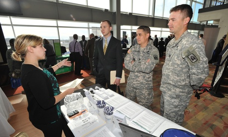 Job-seeking veterans and service members speak with a prospective employer at the Hiring Our Heroes DC job fair at Nationals Park on Dec. 5, 2012 in Washington.