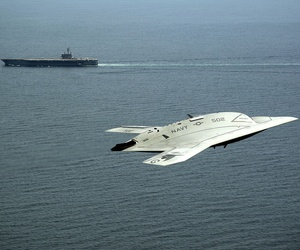 An X-47B drone, part of the Unmanned Combat Air System program, flies past the USS George H.W. Bush during a demonstration on May 14, 2013.