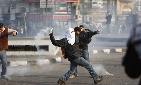 A protestor throws a canister of tear gas during a demonstration in Cairo, Egypt on January 25, 2011