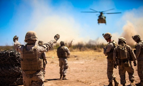 Marines with the 2nd Combat Logistics Battalion direct an Army CH-47 Chinook helicopter during a Network Integration Exercise at Fort Bliss, Texas