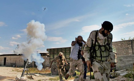 Free Syrian Army fighters take cover after firing a mortar round near Aleppo, Syria.