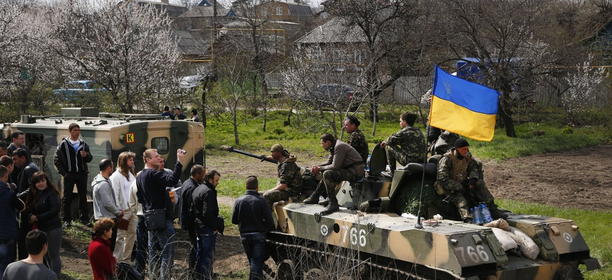 A group of people block a column of Ukrainian Army vehicles en route to Kramatorsk, Ukraine on April 16, 2014.