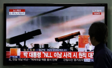 A South Korean man watches a television program reporting on North Korea's live-fire artillery drills on April 29, 2014.