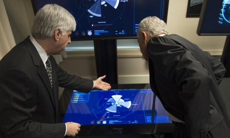 Secretary of Defense Chuck Hagel listens to a brief during a Defense Advanced Research Projects Agency demonstration at the Pentagon April 22, 2014.