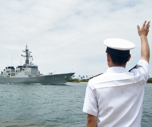 PEARL HARBOR - Republic of Korea Navy Capt. Yong Mo Yang, defense attaché in Hawaii, waves to a Korean destroyer arriving at Joint Base Pearl Harbor-Hickam for the Rim of the Pacific, or RIMPAC, exercise, May 20, 2014.