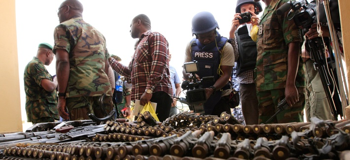 Journalists look at arms and ammunition that military commanders said were seized from Islamic fighters on June 5, 2013, in Maiduguri, Nigeria, near where the radical group Boko Haram kidnapped more than 200 girls in April 2014.