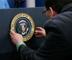 The Presidential seal is adjusted on the podium as last minute details are made before President Barack Obama holds a news conference on July 15, 2011, in the briefing room of the White House.