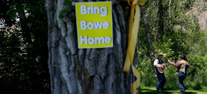 """A yellow ribbon and a sign honoring captive U.S. Army Sgt. Bowe Bergdahl are seen on a tree as J.C. Needham and wife Sonja, right, rehearse to perform at the """"Bring Bowe Back"""" celebration in Hailey, Idaho, June 22, 2013."""