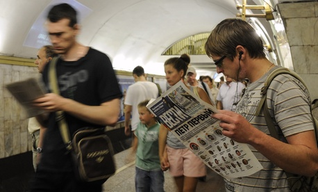 Ukrainians read newspapers at a metro station in Kiev on May 26, 2014.