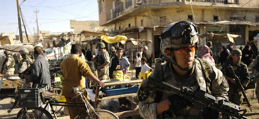An Army specialist move through an open air market during a foot patrol in Baqubah, Iraq, on April 5, 2007.