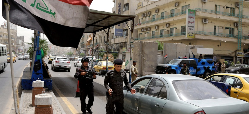 Iraqi federal policemen stand guard at a checkpoint in Baghdad on Wednesday.