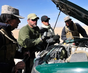 A civilian contractor trains Afghan Border Patrol officers on proper techniques to search a vehicle, on December 21, 2010.