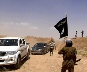 Fighters with the al-Qaeda linked ISIS cross a soil barrier on the Iraq-Syria border, on June 12, 2014.