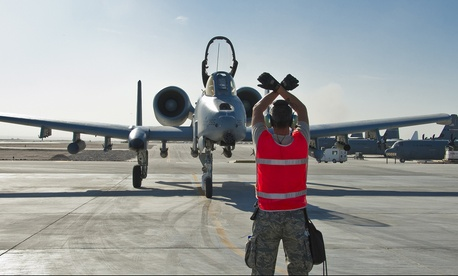 A U.S. Air Force sergeant directs an A-10 Thunderbolt II aircraft for an end of runway inspection, on November 10, 2011.