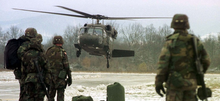 Two U.S. soldiers, members of the NATO mission to Bosnia, wait to board a helicopter, on February 14, 1999.