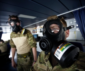 A member of the Danish military dons a protective mask while carrying out emergency drills aboard a frigate, on January 3, 2014.