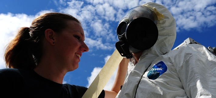An emergency manager from the 628th Civil Engineer Squadron tapes down the mask of an Airman during a simulated dirty bomb attack, Aug. 24, 2012, at Joint Base Charleston, S.C.