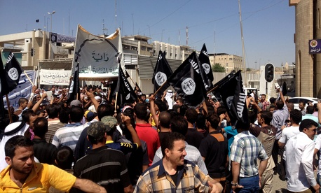 Demonstrators chant pro-al-Qaida-inspired Islamic State of Iraq and the Levant (ISIL) as they wave al-Qaida flags in front of the provincial government headquarters in Mosul, on June 16, 2014.