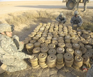 A group of soldiers with the 789th Ordnance Company prepare a cache of landmines and rockets to be disposed of by a high explosives charge near Baghdad, Iraq, on April 13, 2008.